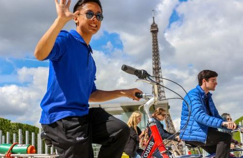 Haolan biking in front of Eiffel Tower on French Exchange with his classmates.